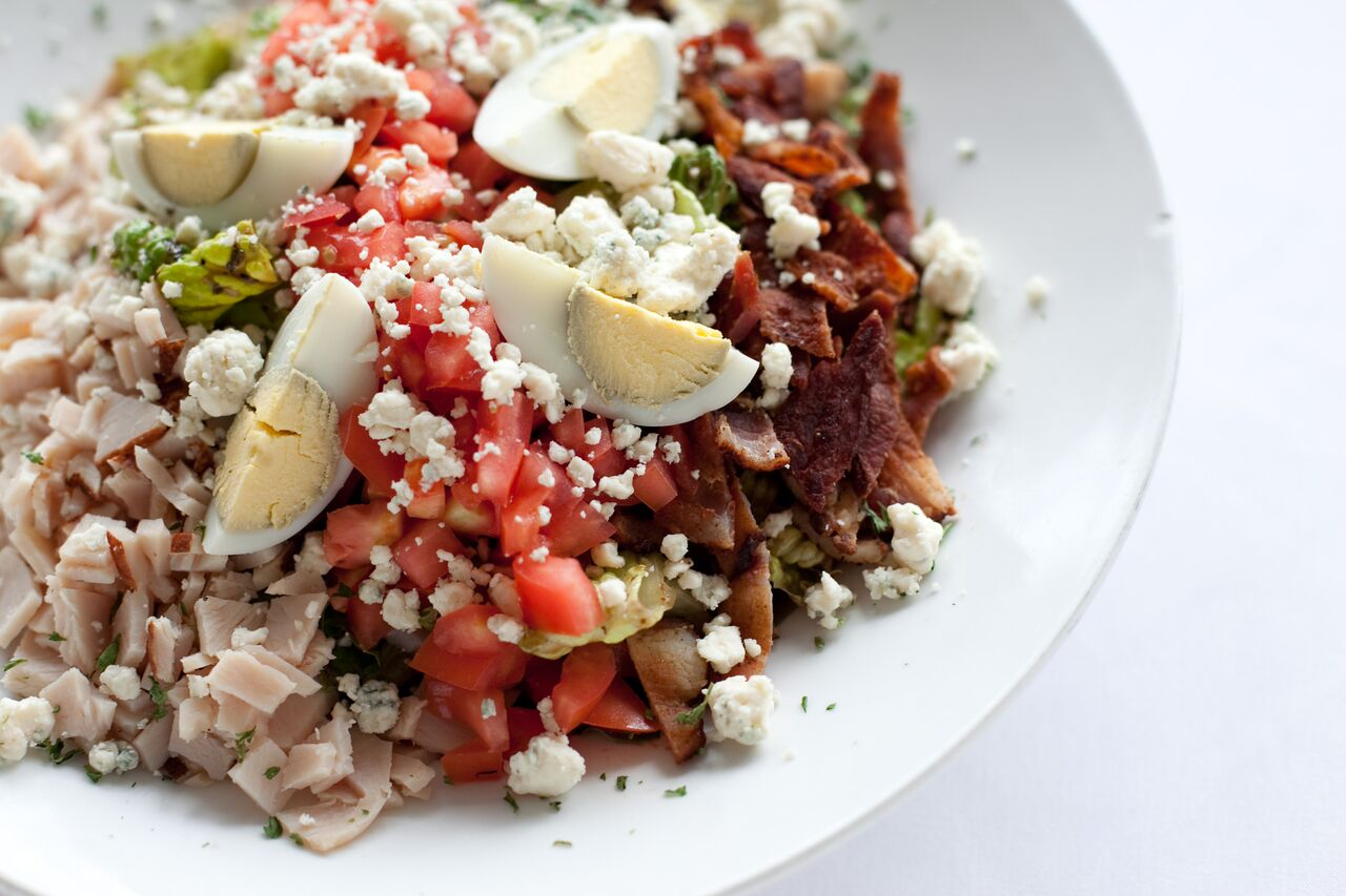Cobb Salad with Turkey, Bacon, Tomatoes, Sliced Hard Boilded Eggs, Crumbled Bleu Cheese over Greens